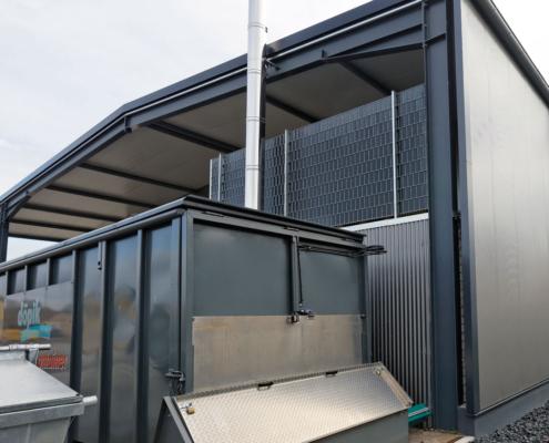 Schubbodencontainer als Hackschnitzellager vor einer Halle mit Edelstahlkamin