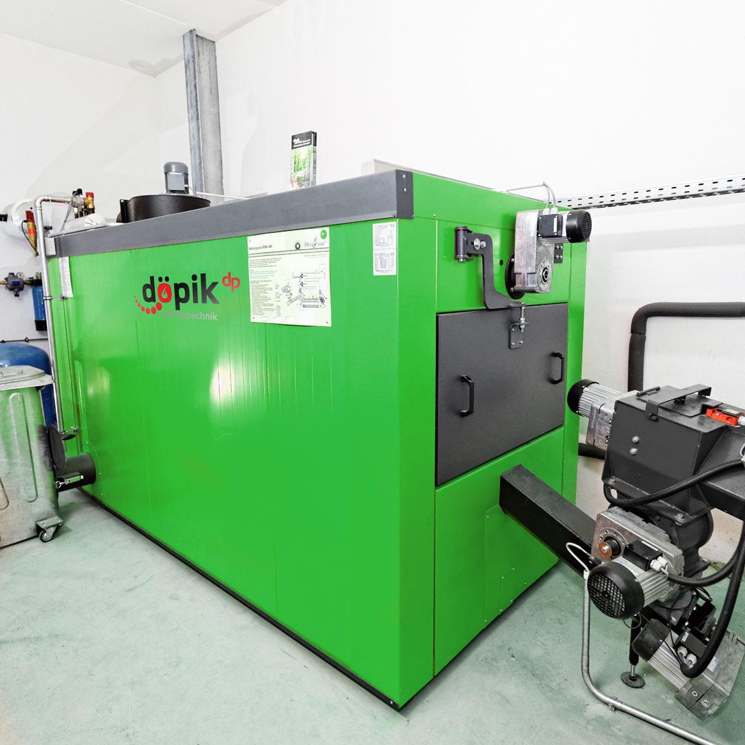 Biomasseheizung mit Zellenradschleuse und Aschetonne in einem Heizraum