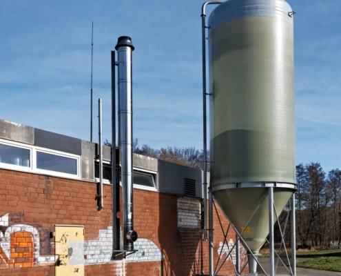 Hochsilo aus GFK zur Pelletlagerung vor einem Industriegebäude