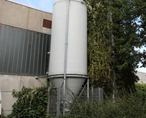 Hochsilo aus glasfaser Kunststoff zur Pelletlagerung vor einem Gebäude und Sträuchern