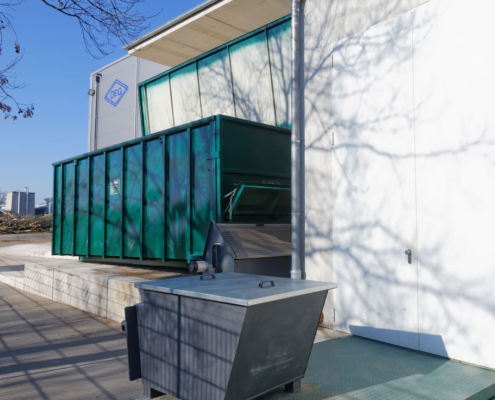 Container an einer Dockingstation als Hackschnitzellager vor einem Gebäude mit blauem Himmel