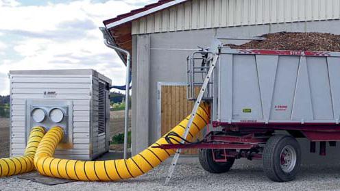 Container auf Rädern mit Hackschnitzeln an einem gelben Schlauch einer Trocknungsanlage
