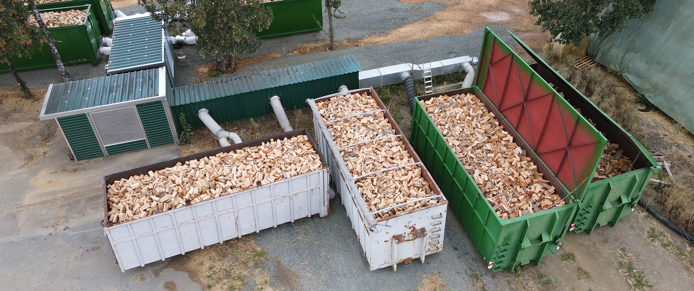 Grüne Metallcontainer gefüllt mit Holz zur Trocknung