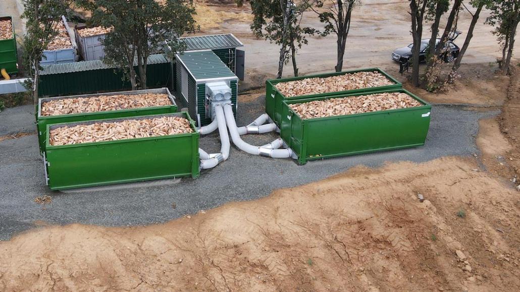 Holztrocknungsanlage mit grünen Containern gefüllt mir Brennholz