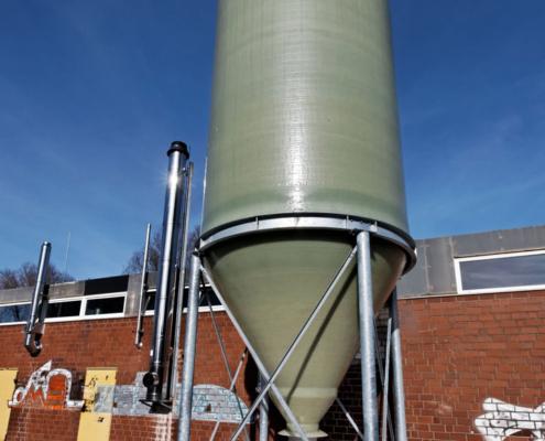 GFK Silo zur Lagerung von Pellets vor einem Industriegebäude mit blauem Himmel