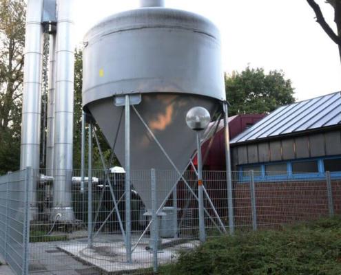 GFK Silo zur Lagerung von Pelltes vor einem Industriegebäude mit Abzugskaminen aus Edelstahl