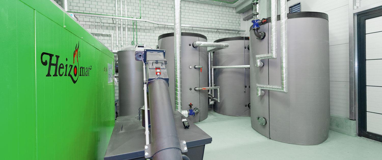 Biomasseheizung und Pufferspeicher in einem gemauerten Heizraum