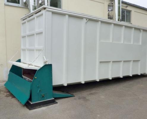 Schubbodencontainer an einer Dockingstation vor einem Gebäude mit Edelstahlkaminen