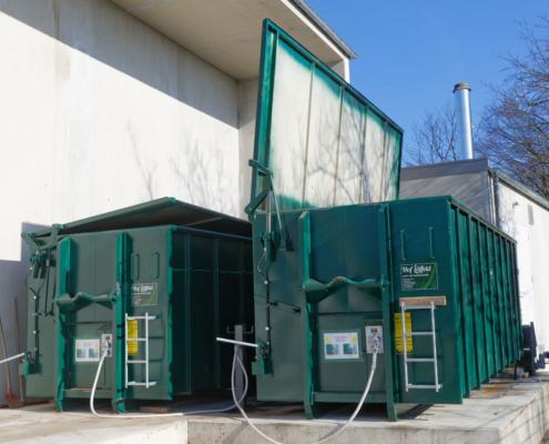Zwei Container an einer Dockingstation als Hackschnitzellager vor einem Gebäude