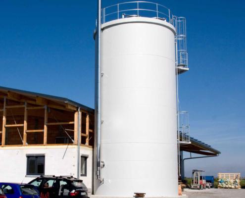 Hochsilo aus Beton zur Lagerung von Hackschnitzeln vor einem Gebäude mit blauem Himmel