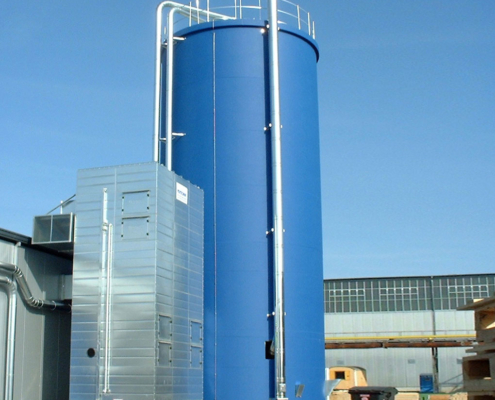 Blaues Hochsilo aus Beton zur Lagerung von Hackschnitzeln vor einem Gebäude mit blauem Himmel