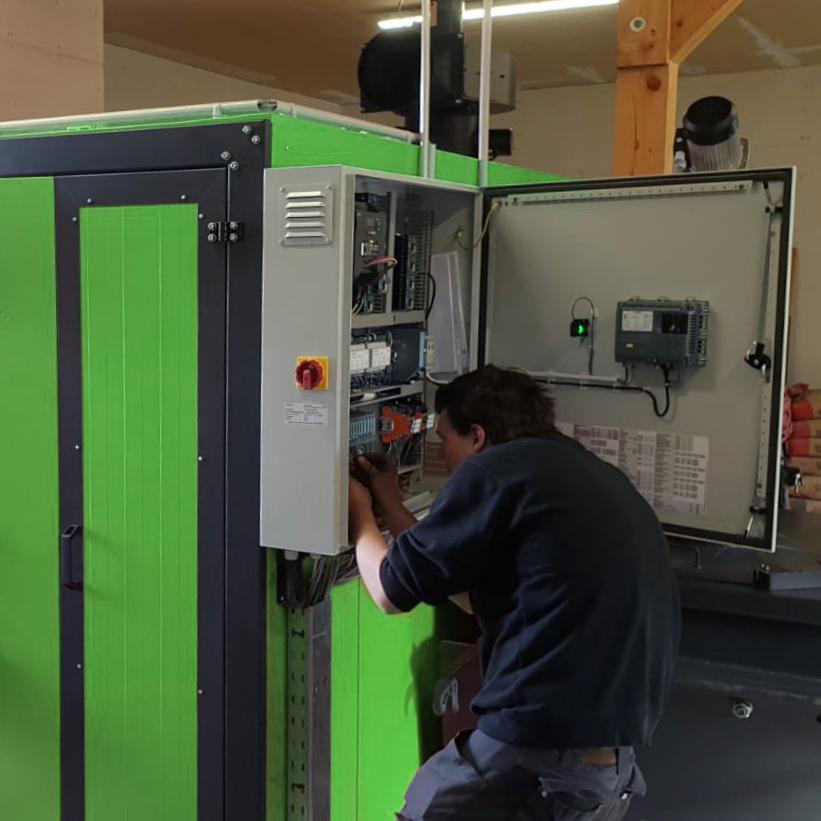 Servicetechniker am Schaltkasten einer grünen Biomasseheizung