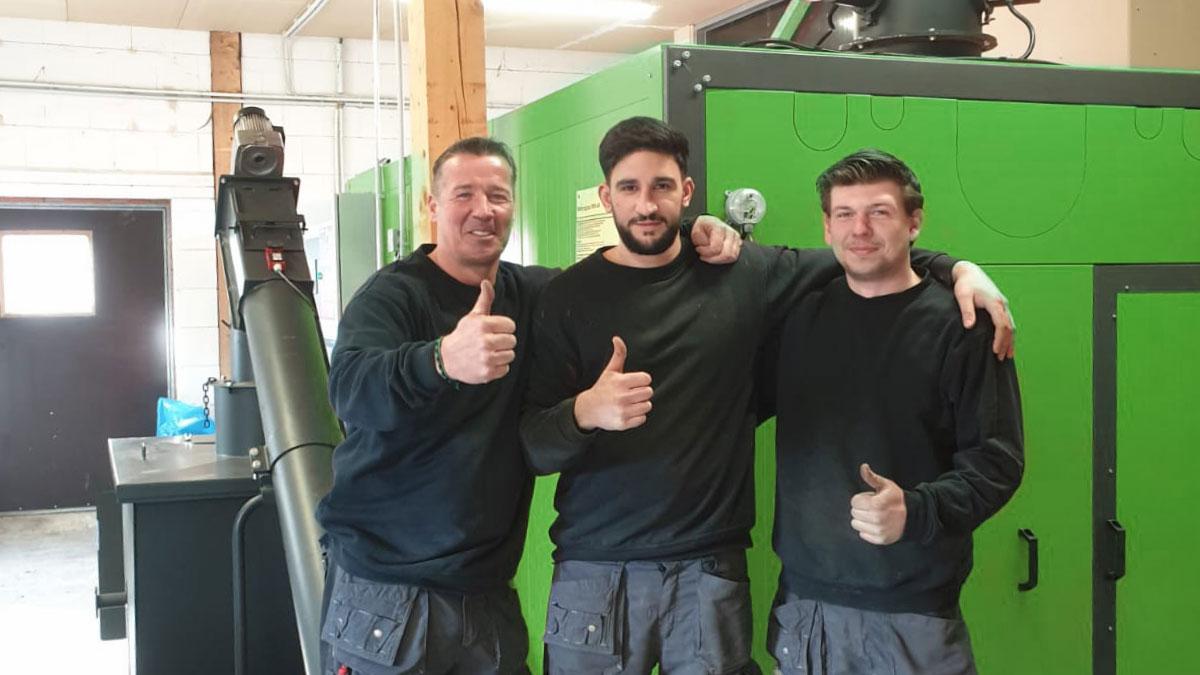 Drei Servicemonteure von döpik nach der Montage einer grünen Biomasseheizung