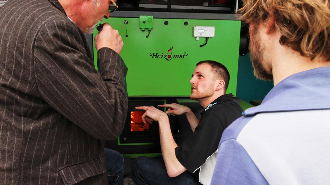 Servicetechniker prüft eine grüne Hackschnitzelheizung