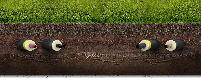 Querschnitt durch eine grüne Wiese mit Fernwärmeleitungen im braunen Erdreich