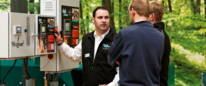 Servicetechniker von döpik erklärt einem Kunden die Steuerung einer Biomasseheizung